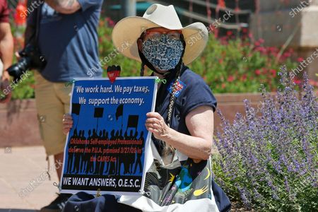 Jennifer Robertson, a self-employed graphic designer from Norman, Okla, holds a sign at the state Capitol to protest the lack of unemployment payments for Pandemic Unemployment Assistance or PUA, for the self employed, in Oklahoma City
