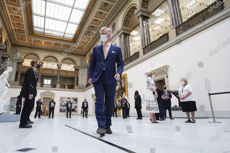 Belgium's King Philippe, center, and Belgium's Queen Mathilde, center right, wear a face mask to prevent the spread of coronavirus, as they visit the Royal Museum of Fine Arts in Brussels, . Museums are hesitantly starting to reopen as the coronavirus lockdown measures are relaxed, yet experts say that one in eight in the world could potentially face permanent closure because of the pandemic