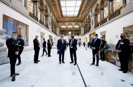 Belgium's King Philippe, center left, wears a face mask, to prevent the spread of coronavirus, as he visits the Royal Museum of Fine Arts in Brussels, . Museums are hesitantly starting to reopen as the coronavirus lockdown measures are relaxed, yet experts say that one in eight in the world could potentially face permanent closure because of the pandemic