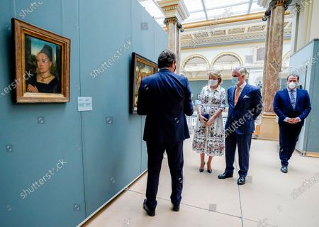 Belgium's King Philippe, center right, and Belgium's Queen Mathilde, center left, wear a face mask to prevent the spread of coronavirus, as they visit the Royal Museum of Fine Arts in Brussels, . Museums are hesitantly starting to reopen as the coronavirus lockdown measures are relaxed, yet experts say that one in eight in the world could potentially face permanent closure because of the pandemic