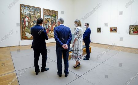 Belgium's King Philippe, center left, and Belgium's Queen Mathilde, center right, wear a face mask to prevent the spread of coronavirus, as they visit the Royal Museum of Fine Arts in Brussels, . Museums are hesitantly starting to reopen as the coronavirus lockdown measures are relaxed, yet experts say that one in eight in the world could potentially face permanent closure because of the pandemic