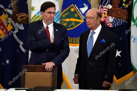 Defense Secretary Mark Esper and Commerce Secretary Wilbur Ross stand as they wait for President Donald Trump to arrive for a Cabinet Meeting in the East Room of the White House, in Washington
