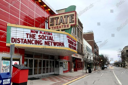 A tongue-in-cheek message is displayed on the marquee of the State Theatre in Traverse City, Mich. The historic theater hosts the Traverse City Film Festival, led by documentary filmmaker Michael Moore, which is among many summer festivals and events in the tourist-friendly community that have been canceled because of the coronavirus. With summer vacation season looming, this town on a Lake Michigan bay normally would be expecting a crush of visitors. But some local residents have mixed feelings about crowds descending on the area, which might cause the number of virus cases to rise