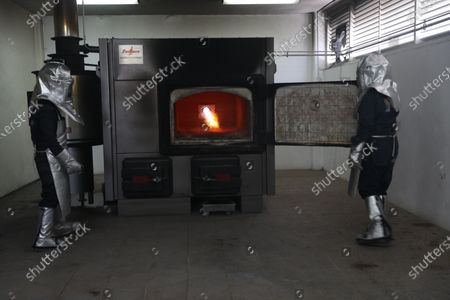 Workers Victor Manuel (L) and Juan Carlos (R) prepare a cremation oven in the municipality of Nezahualcoyotl, in the State of Mexico, Mexico, 18 May 2020 (Issued 19 May 2020). With a helmet, apron and gloves, Victor and Juan work in a crematorium that incinerates to its maximum capacity in the metropolitan area of Mexico City, which totals almost 2,000 deaths by COVID-19 without having yet reached the peak of the pandemic. The municipal pantheon of Nezahualcoyotl, a city adjacent to the Mexican capital, began its cremation service in two ovens at the end of April, in full expansion of the disease, with a capacity for three bodies a day each.