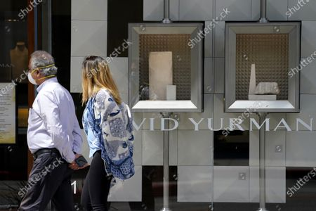 Stock Picture of Couple wearing face masks passes empty display cases at a David Yurman store on Rodeo Drive, in Beverly Hills, Calif
