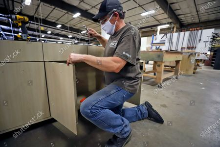 Stock Picture of Kenny Smith of Randolph, N.Y., puts handles on a custom piece of furniture on his first day back at work at Colecraft Commercial Furnishings in Jamestown, N.Y., as part of New York state's Phase One easing of COVID-19 restrictions