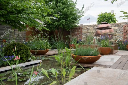 View of pool in The Silent Pool Gin Garden by Neale Richards Design with bronze scuplture and Union Jack of Royal Hospital behind