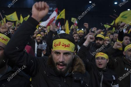 """Supporters of Hezbollah leader Sayyed Hassan Nasrallah chant slogans ahead of the leader's televised speech in a southern suburb of Beirut, Lebanon. The headbands read, """"Death to America."""" Twenty years after Hezbollah guerrillas pushed Israel's last troops from southern Lebanon, both sides are gearing up for a war that neither seems to want. Israeli troops are drilling for a possible invasion of Lebanon and striking Hezbollah targets in neighboring Syria. Hezbollah is beefing up its own forces and threatening to invade Israel"""