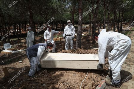Stock Image of Cemetery workers bury the coffin of Lutfiye Yilmaz, who died from COVID-19-related illness, during her funeral ceremony at the Kilyos Cemetery in Istanbul, Turkey, 18 May 2020 (issued 20 May 2020). The toll from coronavirus-related deaths has risen in Turkey to 4,199 people as of 19 May 2020, with the country reporting 151,615 confirmed cases. Twenty-four healthcare and medical workers have died since the beginning of the outbreak, and more than 7,400 have been infected with the novel SARS-CoV-2 coronavirus that causes the COVID-19 disease. President Erdogan announced a curfew in 81 Turkish cities, including Istanbul, from 23 to 26 May 2020 to curb the spread of the ongoing pandemic. The lockdown coincides with the festival of Eid al-Fitr, which marks the end of the Muslim fasting month of Ramadan.
