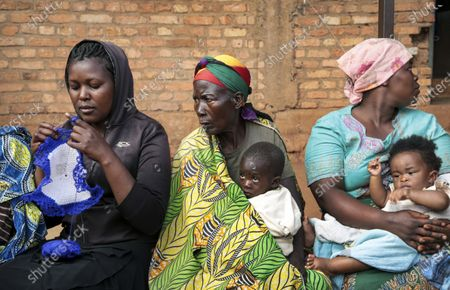 """Woman knits and others hold babies as they wait to cast their votes in the presidential election, in Giheta, Gitega province, Burundi, . A crucial election has begun in the East African nation of Burundi, where President Pierre Nkurunziza is stepping aside after a divisive 15-year rule but will remain """"paramount leader"""" in the country that continues to reject outside scrutiny"""
