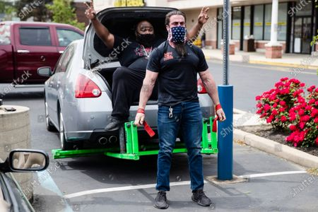 Stock Picture of Atilis Gym co-owners Ian Smith lifts the rear end of a car with Tiny Richardson in the trunk outside of his gym in Bellmawr, N.J., . The gym in New Jersey reopened for business early Monday, defying a state order that shut down nonessential businesses to help stem the spread of the coronavirus