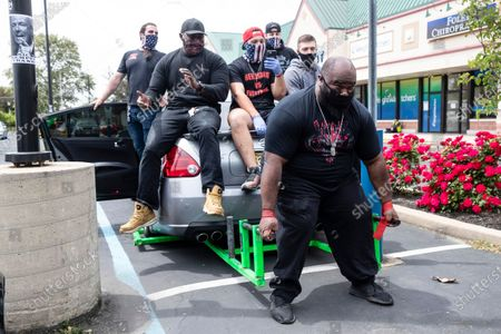 Tiny Richardson attempts to lift the rear end of a car along with Atilis Gym co-owners Ian Smith, back left, and others out side of the gym in Bellmawr, N.J., . The gym in New Jersey reopened for business early Monday, defying a state order that shut down nonessential businesses to help stem the spread of the coronavirus