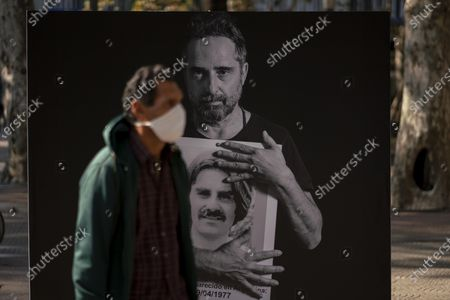 Stock Image of Man wearing a face mask passes a large photo of Uruguayan singer and songwriter Jorge Drexler holding a smaller photo of Andres Bellizzi, who disappeared during the military dictatorship (1973-1985), in downtown Montevideo, Uruguay, the day two lawmakers were murdered in 1976. Wednesday marks the 25th anniversary of an annual march that remembers those who were disappeared and murdered during the dictatorship, but this year's march will not take place due to measures to contain the spread of new coronavirus