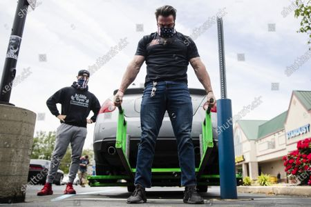 Stock Image of Atilis Gym co-owner Ian Smith lifts the rear end of a car outside of his gym in Bellmawr, N.J., . The owners of the southern New Jersey gym was again been cited Tuesday for reopening the business in defiance of a state order that shut down nonessential businesses to help stem the spread of the coronavirus