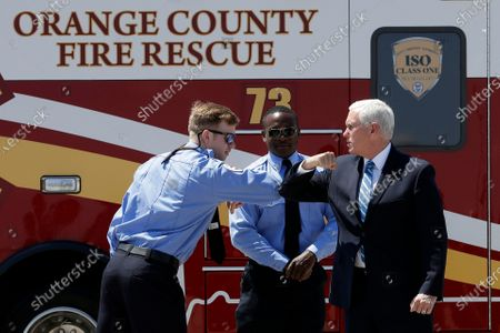 Vice President Mike Pence, right, greets paramedics after arriving at the airport, in Orlando, Fla. Pence is scheduled to participate in a roundtable discussion with hospitality and tourism industry leaders to discuss their plans for re-opening