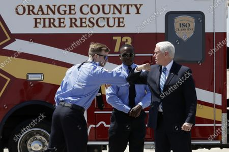 Vice President Mike Pence, right, greets paramedics after arriving at the Orlando International Airport, in Orlando, Fla. Pence is scheduled to participate in a roundtable discussion with hospitality and tourism industry leaders to discuss their plans for re-opening during the coronavirus outbreak