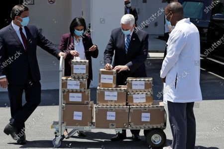 Vice President Mike Pence, second from right, writes on a box after delivering personal protective equipment to the Westminster Baldwin Park, in Orlando, Fla., as part of the initiative to deliver PPE to more than 15,000 nursing homes across America. Looking on is Florida Gov. Ron DeSantis, left, Seema Verma, the Administrator for the Centers for Medicare and Medicaid Services, second from left, and Healthcare Administrator Fanley Romelus, right