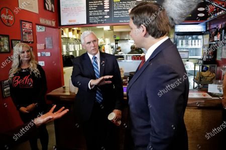 Vice President Mike Pence, center, gestures as he speaks to Florida Gov. Ron DeSantis, right, after ordering lunch at Beth's Burger Bar, in Orlando, Fla. Pence is scheduled to participate in a roundtable discussion with hospitality and tourism industry leaders to discuss their plans for re-opening during the coronavirus outbreak