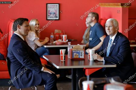 Vice President Mike Pence, right, talks to Florida Gov. Ron DeSantis as they wait for their lunch at Beth's Burger Bar, in Orlando, Fla. Pence is scheduled to participate in a roundtable discussion with hospitality and tourism industry leaders to discuss their plans for re-opening during the coronavirus outbreak