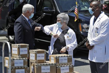 Vice President Mike Pence, left, greets director of nursing Shirley Schultz and health service administrator Fanley Romelus, right, after delivering personal protective equipment to the Westminster Baldwin Park, in Orlando, Fla., as part of the initiative to deliver PPE to more than 15,000 nursing homes across America. Pence is also scheduled to participate in a roundtable discussion with hospitality and tourism industry leaders to discuss their plans for re-opening the coronavirus outbreak