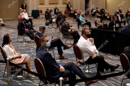 Visitors practice social distancing as they listen to Vice President Mike Pence participate in a roundtable discussion with hospitality and tourism industry leaders to discuss their plans for re-opening during the coronavirus outbreak, in Orlando, Fla