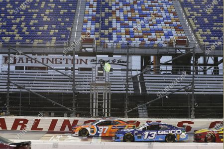 Ryan Preece (37) leads Ty Dillon (13) as the green flag is waved in front of empty seats at the start of the NASCAR Cup Series auto race, in Darlington, S.C