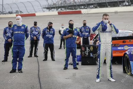 Driver Ty Dillon, right, stands for the national anthem before the start of the Toyota 500 NASCAR Cup Series auto race, in Darlington, Tenn