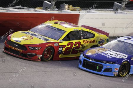 Joey Logano (22) leads Ty Dillon (13) during the NASCAR Cup Series auto race, in Darlington, S.C
