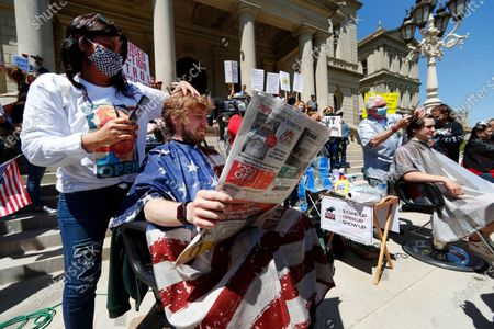 Jody Hebberd, left, gives a free haircut to Reid Scott, as he reads the paper on the steps of the State Capitol as Karl Manke, right, cuts the hair of Parker Shonts during a rally in Lansing, Mich., . Barbers and hair stylists are protesting the state's stay-at-home orders, a defiant demonstration that reflects how salons have become a symbol for small businesses that are eager to reopen two months after the COVID-19 pandemic began