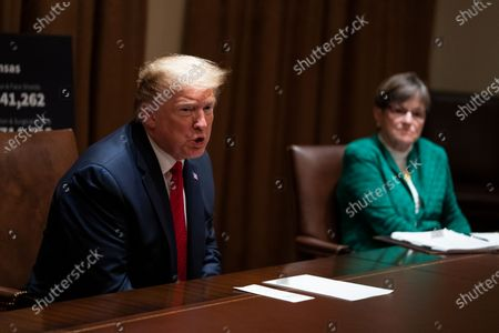Kansas Gov. Laura Kelly listens as President Donald Trump speaks during a meeting in the Cabinet Room of the White House, in Washington