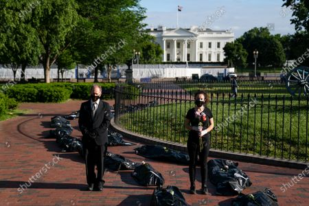Michael Beer, of Arlington, Va., left, and Margot Bloch, of Takoma Park, Md., take part in a demonstration on the Trump administration response to the coronavirus pandemic, in front of the White House, in Washington