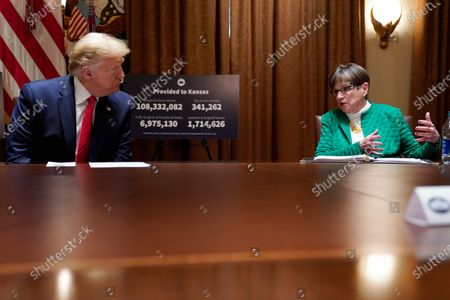 President Donald Trump listens during a meeting Kansas Gov. Laura Kelly, right, in the Cabinet Room of the White House, in Washington