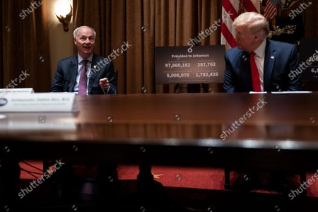 President Donald Trump listens as Arkansas Gov. Asa Hutchinson speaks during a meeting in the Cabinet Room of the White House, in Washington