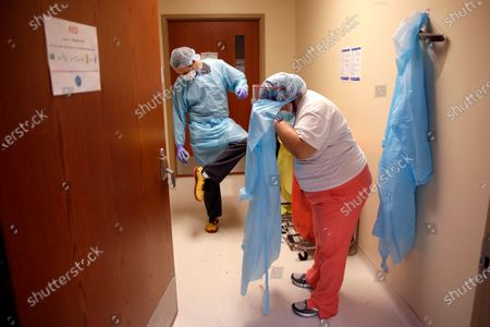 Dr. Drew Miller sprays disinfectant on his shoes while respiratory therapist Jade Carabajal-Richter removes protective gear after checking on COVID-19 patients at Kearny County Hospital in Lakin, Kan. The rural 24-bed hospital is currently treating five patients for COVID-19 while the county has seen a spike in cases due to clusters in nearby meatpacking plants