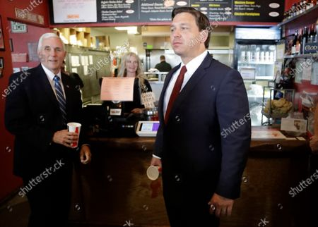 Stock Photo of Vice President Mike Pence, left, and Florida Gov. Ron DeSantis arrive for lunch at Beth's Burger Bar, in Orlando, Fla. Pence is also scheduled to participate in a roundtable discussion with hospitality and tourism industry leaders to discuss their plans for re-opening