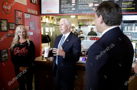 Vice President Mike Pence, center, and Florida Gov. Ron DeSantis eat lunch at Beth's Burger Bar, in Orlando, Fla. Pence is also scheduled to participate in a roundtable discussion with hospitality and tourism industry leaders to discuss their plans for re-opening