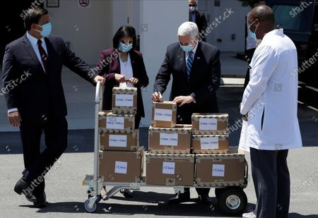 Vice President Mike Pence, second from right, Seema Verma, Administrator of the Centers for Medicare and Medicaid, second from left, and Florida Gov. Ron DeSantis, left, deliver personal protective equipment to a nursing home, in Orlando, Fla., as part of the initiative to deliver PPE to more than 15,000 nursing homes across America. Pence is also scheduled to participate in a roundtable discussion with hospitality and tourism industry leaders to discuss their plans for re-opening during the coronavirus outbreak