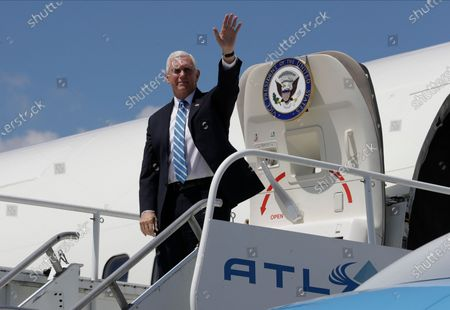 Vice President Mike Pence waves as he arrives at the Orlando International Airport, in Orlando, Fla. Pence is scheduled to participate in a roundtable discussion with hospitality and tourism industry leaders to discuss their plans for re-opening during the coronavirus outbreak