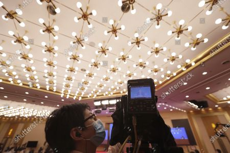 A journalist operates a camera as he attends a news conference by Zhang Yesui, a spokesman for the National People's Congress, broadcasted remotely to the media center on the eve of the annual legislature opening session in Beijing, China, 21 May 2020. The holding of the 'two sessions' as the annual meetings are known, is a further sign of what the ruling Communist Party says is its success in bringing the outbreak under control, though clusters of cases are still popping up in some parts of the country.  China will hold the Chinese People's Political Consultative Conference (CPPCC) on 21 May and the National People's Congress (NPC) on 22 May, after the two major political meetings initially planned to be held in March 2020 were postponed amid the ongoing coronavirus COVID-19 pandemic.