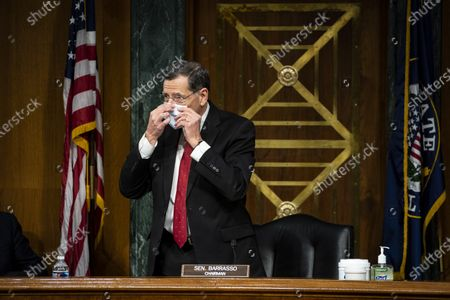 United States Senator John Barrasso (Republican of Wyoming) and chairman of the US Senate Environment and Public Works Committee, puts on a face mask as he departs following a hearing, on Capitol Hill in Washington, D.C., U.S.,.