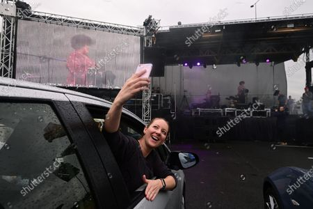 A person takes a selfie as guests watch on from their vehicles Casey Donovan (on stage) performing during a drive-in concert at the Robyn Webster Sports Centre in Sydney, New South Wales, Australia, 21 May 2020. The concert was organized as part of the music industry's effort to return to live shows without defying coronavirus restrictions. Up to 600 people were allowed to attend the event.