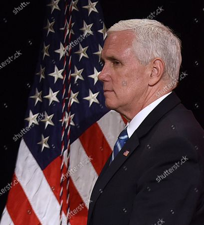 U.S. Vice President Mike Pence walks past an American flag after participating in a roundtable discussion with Florida Gov. Ron DeSantis and hospitality and tourism industry leaders to discuss Florida's phased economic reopening during the coronavirus pandemic.