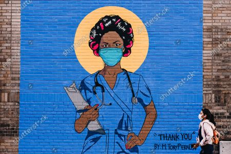 A pedestrian wearing a protective mask walks by a mural of a nurse outside NewYork-Presbyterian / Columbia University Medical Center during the coronavirus pandemic.