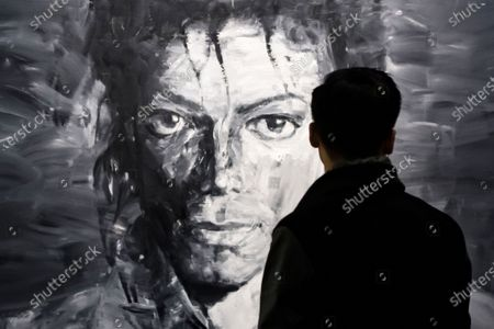 Stock Picture of A visitor looks at a grey and black colored artwork of Yan Pei-Ming displayed as part of the 'Michael Jackson: On the Wall' exhibition at the Grand Palais in Paris, France, 21 November 2018 (reissued 21 May 2020). Considered to be a neutral and unemotional color, grey is most commonly associated with architecture, smoke, and grey-clouded sky. In psychology, grey symbolizes intellect, knowledge and wisdom but is also associated with old age and loss or depression. It can appear conservative and boring on one hand and calming and sophisticated on the other. With its many shades, grey is the color of compromise - neither black nor white.