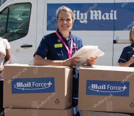 Stock Image of Stevenage, Mail Force protective equipment for healthcare workers. Their arrival marked the end of a 2,000-mile, week-long journey across the continent from Turkey. In their cargo were 100,000 gowns bought by the Mail Force charity to help solve the PPE crisis. Staff at the Lister Hospital in Stevenage, pictured receiving the latest delivery of PPE provided by Daily Mail reader donations to the charity Mail Force. The delivery included Turkish made gowns which arrived in the UK last weekend.  Left to right are Porter Ian Kelsey, Nurse Lorraine Williams, Director of Nursing Rachael Corser, Nurse Anette Overman, Porter Kevin Chambers, Nurse Mae Cometa, and Porter Mark Antoni.