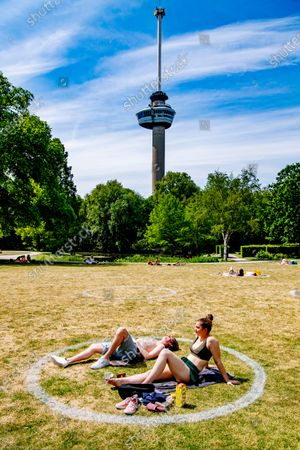 Sunbathing in the park during Ascension Day. Special one and a half meter circles to help people keep their distance from each other. In the Vroesenpark, Het Park at the Euromast and the Kralingse Bos, Stadsbeheer has made circles with which you can clearly define your own 'aura' so that other people do not get too close.