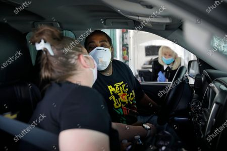 """Kerri Sims, left, and Christopher McCall of Las Vegas lean in to kiss each other while wearing masks at their drive-thru wedding at A Little White Wedding Chapel, in Las Vegas. """"This is definitely not how we planned to get married, but what can you do?"""" said Sims"""
