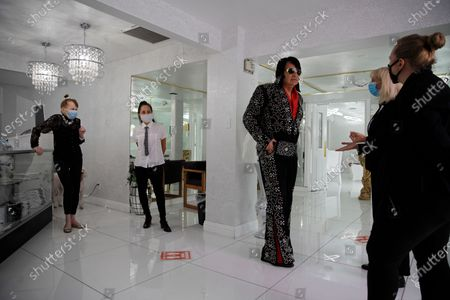 Owner Charolette Richards, left, watches as Elvis impersonator Michael Conti waits before performing a wedding at A Little White Wedding Chapel, in Las Vegas