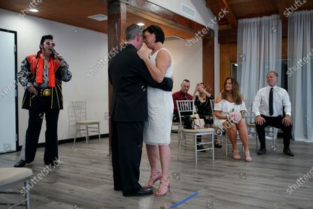 Stock Image of Charles King sings as Elvis as he marries Alicia Funk, center right, and Vaughan Chambers at A Little Wedding Chapel, in Las Vegas. The couple, from Chicago, originally planned to get married in April, but disruptions from the coronavirus caused them to move the wedding to May with only a few guests