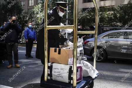Stock Picture of Personal belongings delivered from the vehicle Michael Cohen arrived in are brought into his Manhattan apartment building, in New York. President Donald Trump's longtime personal lawyer and fixer was released federal prison Thursday and is expected to serve the remainder of his sentence at home. Cohen has been serving a federal prison sentence at FCI Otisville in New York after pleading guilty to numerous charges, including campaign finance fraud and lying to Congress
